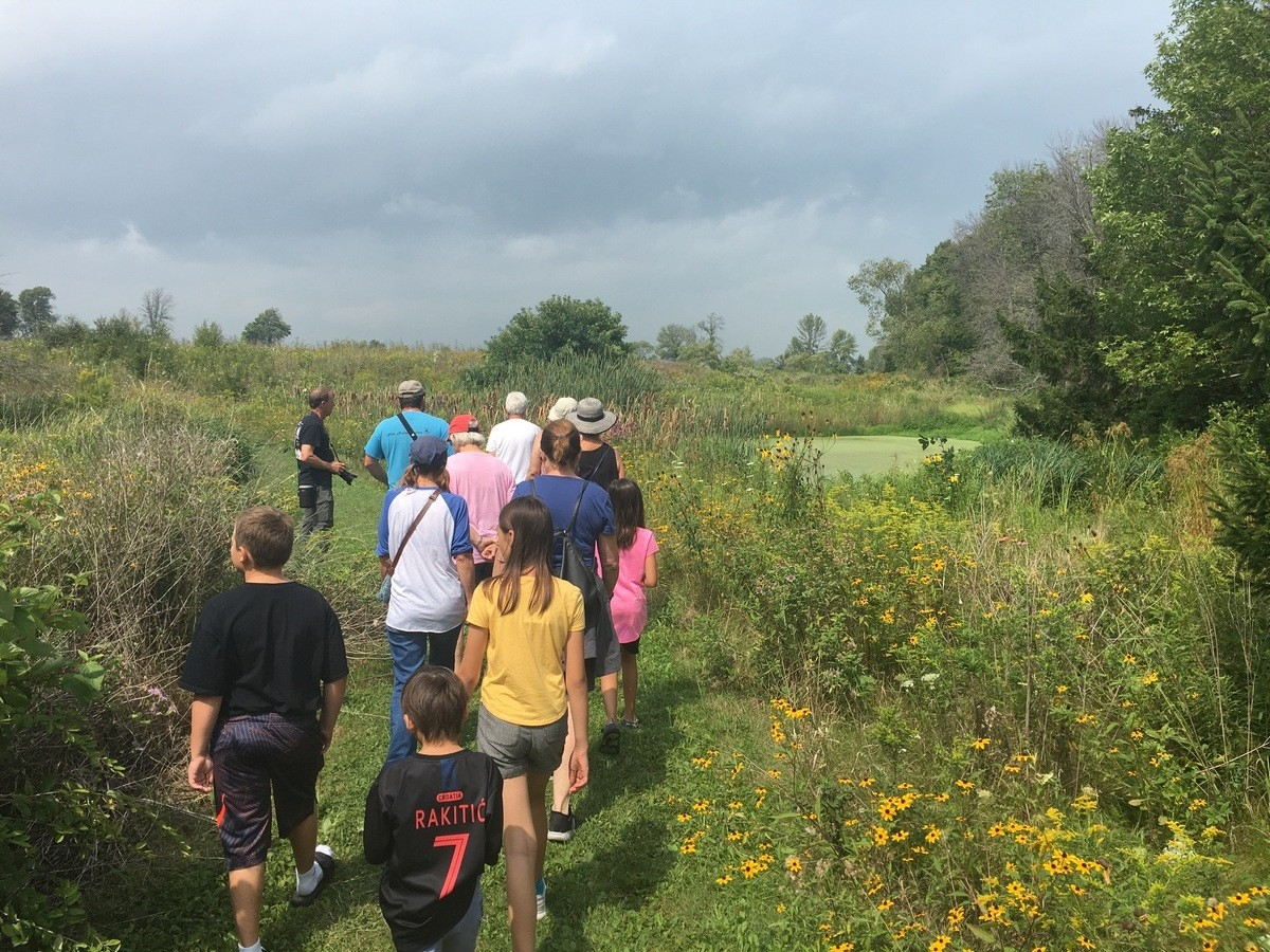 Group of people hiking through a prairie with flowers.