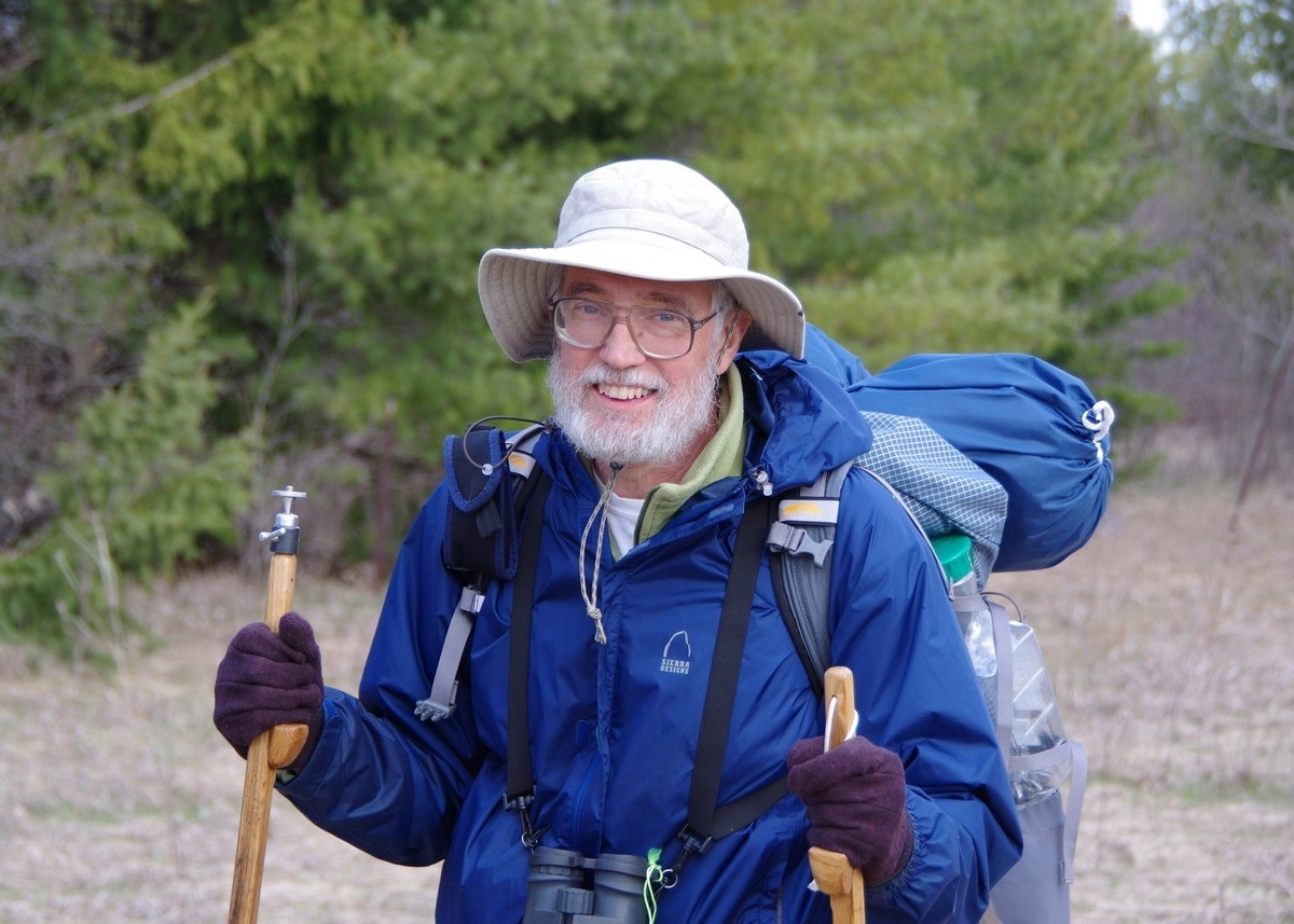 Man in hat with hiking gear.
